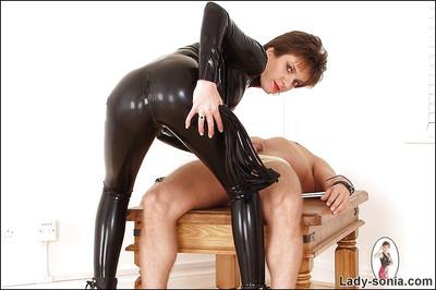 Kinky mature lady in latex outfit playing with her human pet