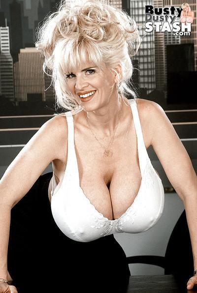 Older blonde babe Busty Dusty baring huge juggs at secretary desk in office