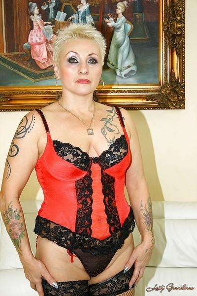 Mature blonde in stockings shows her tattooed body and her wet cunt