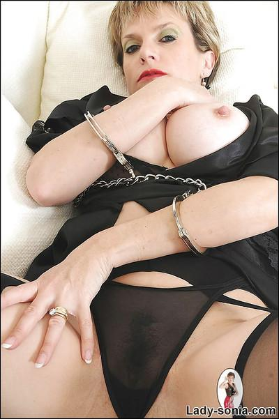 Gorgeous mature lady with huge boobs posing with her hands in handcuffs