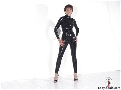 Seductive mature fetish babe on high heels posing in latex suit
