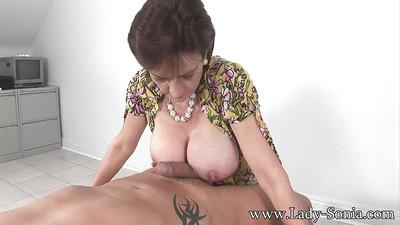 Mature femdom gives a great tugjob and gets her boobies glazed with cum