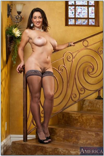 Mature lady Persia Monir stripping to stockings and heels on the stairs