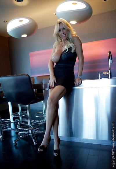 Mature bombshell in tiny dress uncovering her huge jugs and inviting gash