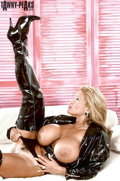 Mature pornstar Tawny Peaks flaunting massive tits in latex stripper boots