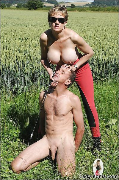 Topless mature femdom in red tights torturing her male pet