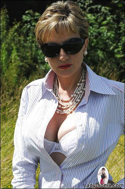 Busty mature femdom in sunglasses tortures her boyslave outdoor
