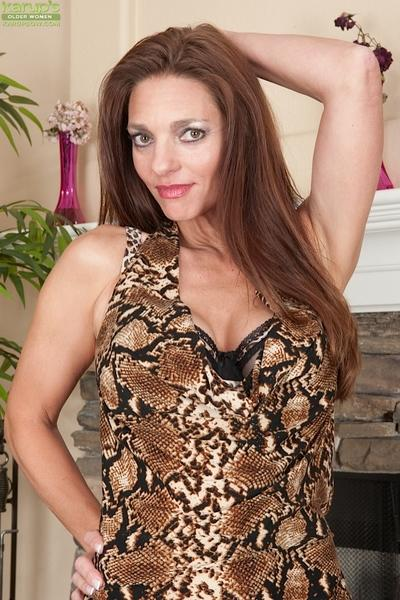 Mature babe Mindi Mink reveals her big tits and pussy while undressing