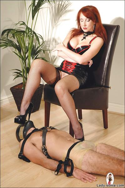 Mature fetish lady in latex dress torturing her male pet