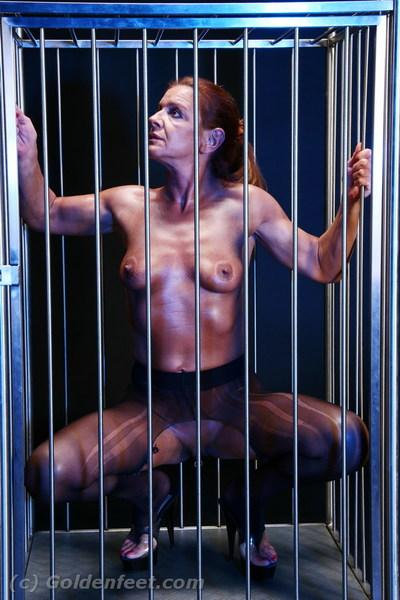 Aged fetish model Lady Sarah revealing pierced pussy in jail cell