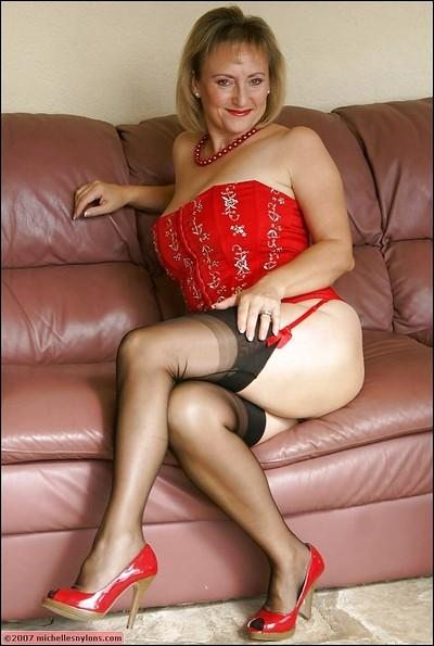 Busty mature lady in stockings and red corset strips down to expose her big boobs