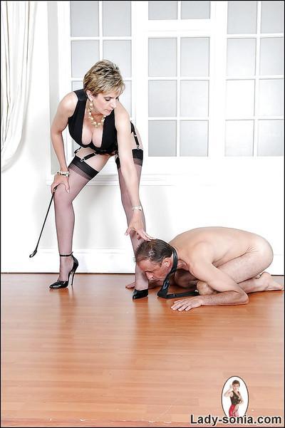 Busty mature femdom on high heels tortures her naked manslave