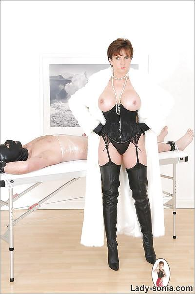 Sexy femdom in black boots gives a handjob to her boyslave