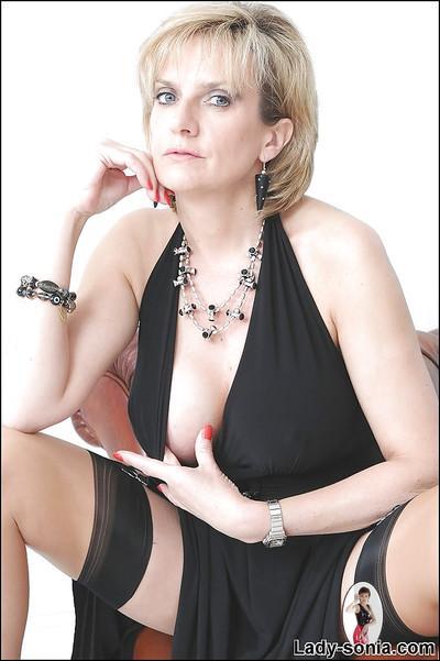 Stunning mature babe posing on the sofa and masturbating her twat