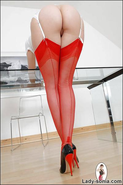 Bottomless mature lady in red stockings exposing her ample ass