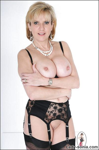 Blonde mature fetish babe in stockings exposing her big jugs