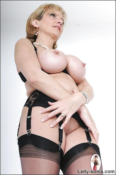 Blonde mature fetish babe in stockings exposing her big jugs
