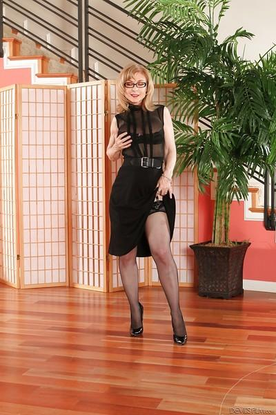 Mature cutie with long legs Nina Hartley shows off in stockings