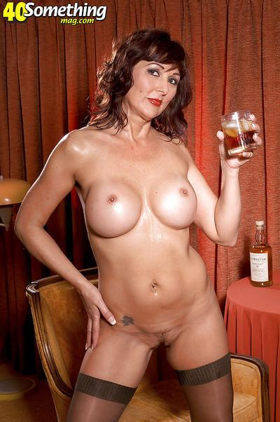 Busty mom in nylon stockings Desi Foxx enjoying whiskey and cigar while stripping