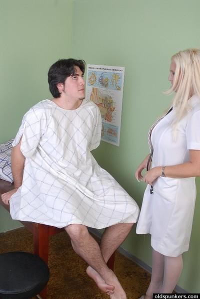 Buxom older nurse Kayla Kupcakes attacks younger man with massive tits