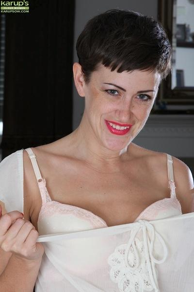 Skinny short haired brunette solo girl Stevie Jones baring small MILF boobs