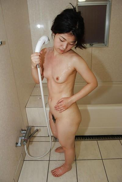 Brunette milf Yuko Goto teases her wet Asian pussy in bathroom