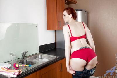 Naughty redhead MILF with bushy twat getting nude in the kitchen