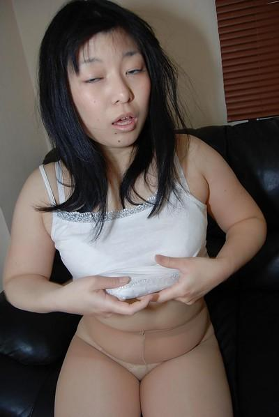Dark haired Asian milf Shinobu Kawahara strips to play with her cunt