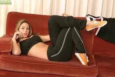 Alluring lady Abigail is posing in her yoga pants on the red sofa