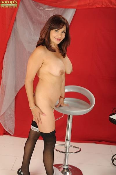 Busty mature maid in black nylons revealing her inviting pussy