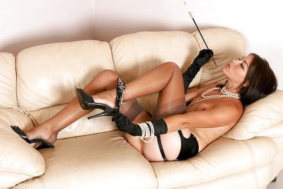Mature MILF in nylons and garters enjoying a smoke in long black gloves