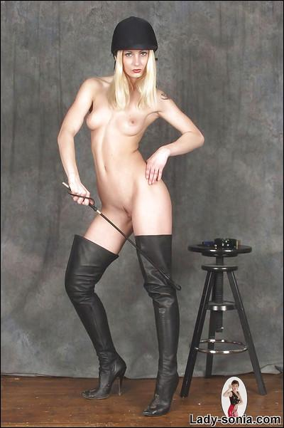 Naked blonde babe in black boots showcasing her fuckable body