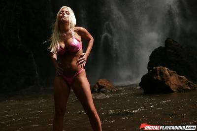 Blonde milf Jesse Jane is posing with naked boobies in front waterfall