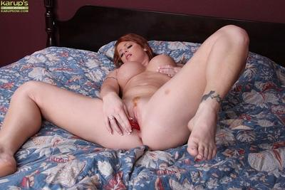 Curvaceous redhead MILF Sara Orlando toying her pink pussy on the bed