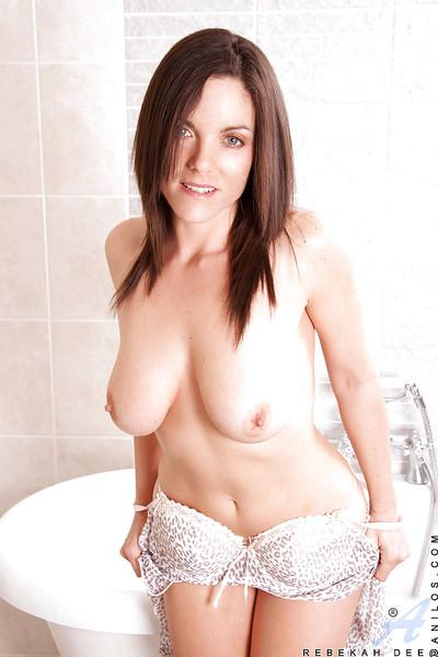 Busty MILF Rebekah Dee fondling her nice tits and twat in the bathroom