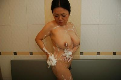 Busty asian MILF taking bath and rubbing her soapy cunt in close up