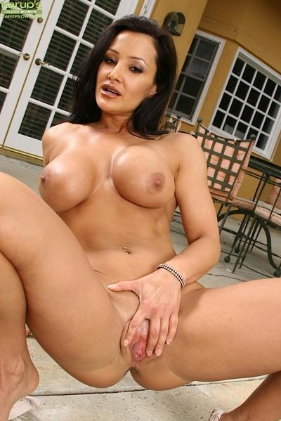 Brunette MILF Lisa Ann fondling big boobs outdoors while spreading vagina