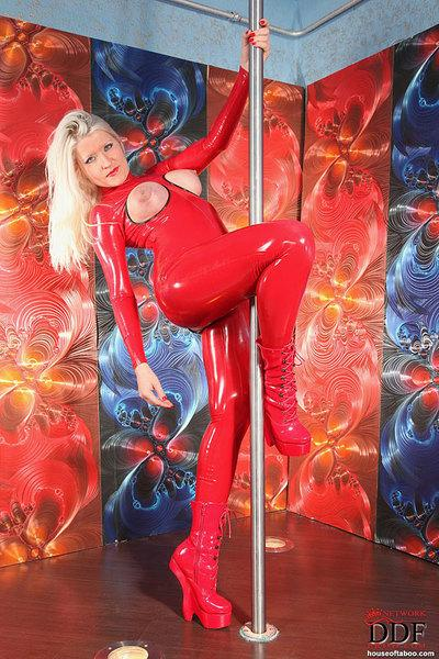 Blond MILF in red full body latex catsuit posing and spreading pussy