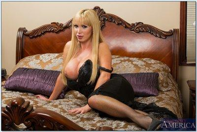 Busty MILF in stockings Nikki Benz stripping and spreading her legs