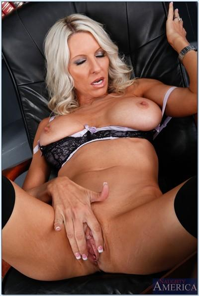 Busty MILF babe Emma Starr strips to stockings to show her wet cunt