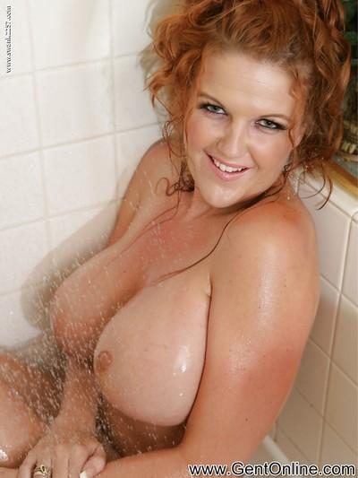 Redhead MILF with huge round jugs pleasing her gash with shower jets
