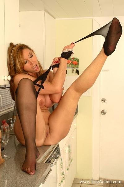 Curvy MILF in stockings stripping off her maid uniform in the kitchen