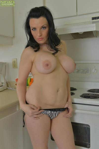 Busty brunette mom Stacy Ray slips off denim skirt and panties in kitchen