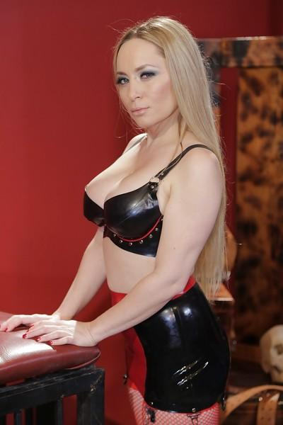Busty blonde fetish model Aiden Starr strutting in latex mini skirt