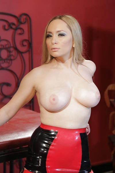 Busty blonde fetish model Aiden Starr strutting in latex mini skirt