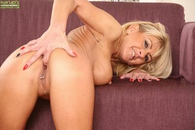 Older Cathie, a blonde milf on high heels and skirt, spreads her pussy