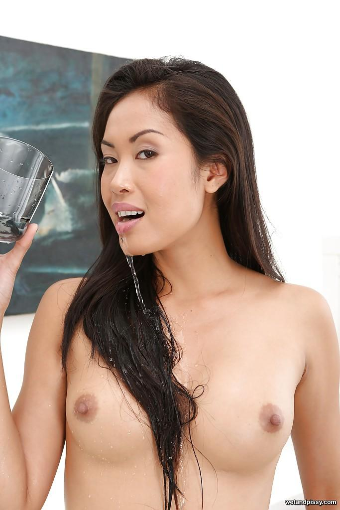 Asian milf pissing in a cup