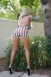 Sassy MILF in tiny dress and sunglasses exposing her goods outdoor