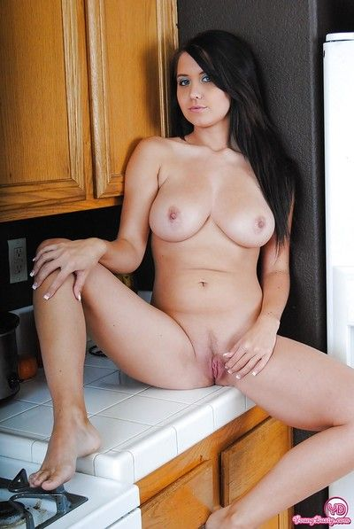 Young and busty suntanned beauty showing off pink twat in kitchen