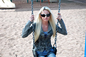 Blond youthful is at the park and this girl looks joyful in her sunglasses